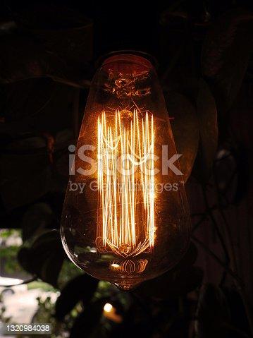close up transparent tungsten light bulb in dark background