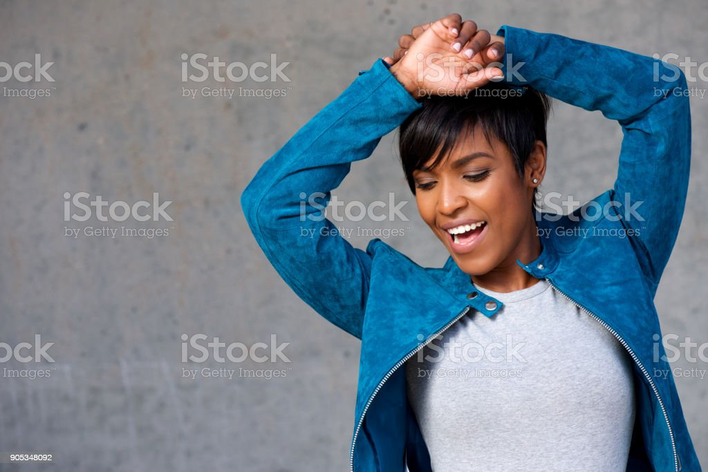 Close up trendy young black woman smiling against gray wall stock photo