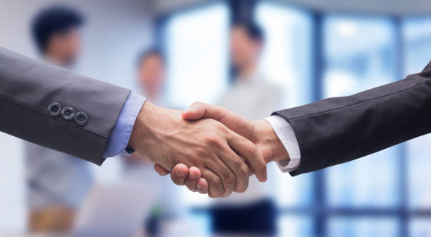 close up two businessman hand shake together for agreement successful on blur group of businesspeople talking in meeting room , achievement concept - legame affettivo foto e immagini stock