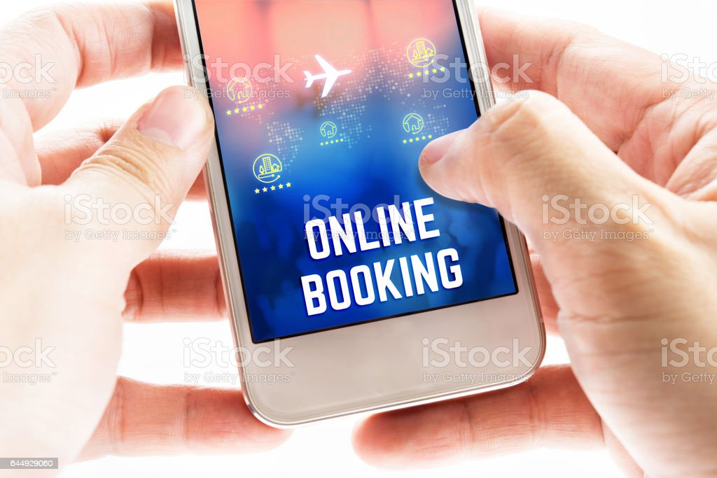 Close up Two hand holding mobile phone with online booking word and icons, Online Digital Marketing concept stock photo