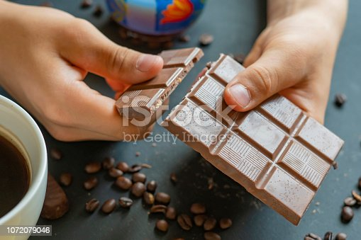 istock close up two hands crack a chocolate bar with coffee cup f 1072079046