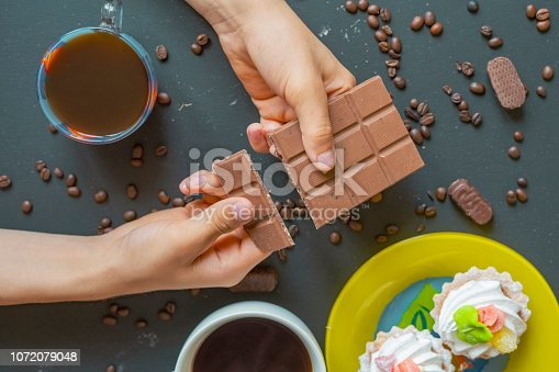 istock close up two hands crack a chocolate bar with coffee cup f 1072079048