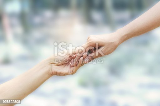 1035928092istockphoto close up two hands reaching and pulling for helping and rescue concept for international day of peace. 958322808