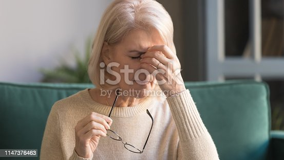 1049512672 istock photo Close up unhappy grey haired mature woman suffering from eyestrain 1147376463