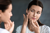 Close up unhappy sad woman looking at red acne spots on chin in mirror, upset young female dissatisfied by unhealthy skin, touching, checking dry irritated face skin, skincare and treatment concept