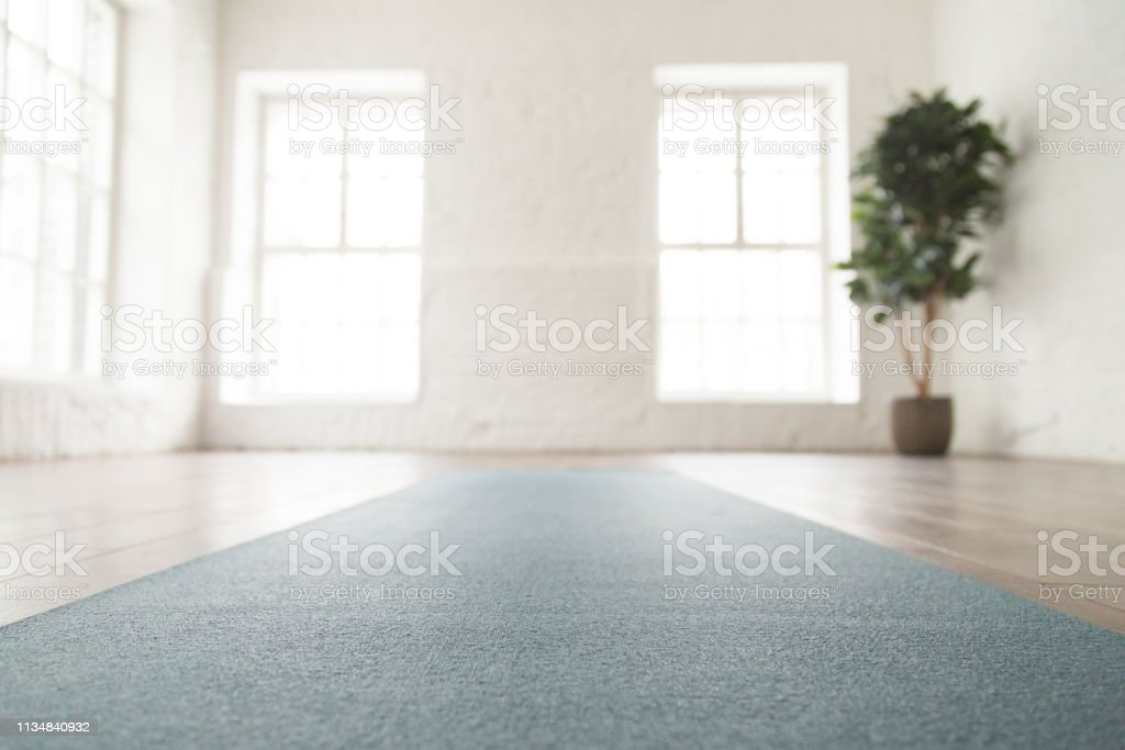 Close up unrolled yoga mat on floor in empty room Close up unrolled yoga mat on wooden floor in empty room, modern yoga studio or fitness center with big windows and white brick walls, sport equipment for meditating or exercises Aerobics Stock Photo