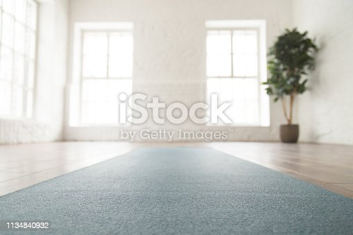 istock Close up unrolled yoga mat on floor in empty room 1134840932