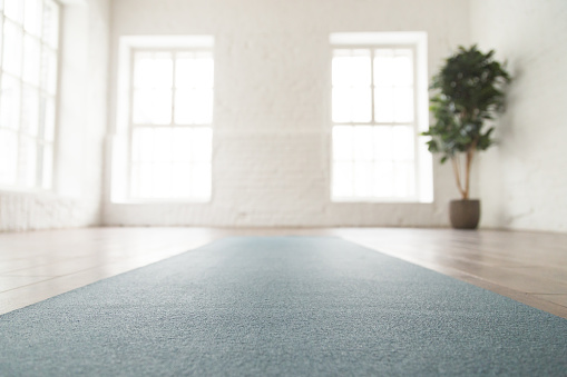 Close Up Unrolled Yoga Mat On Floor In Empty Room Stock Photo - Download Image Now