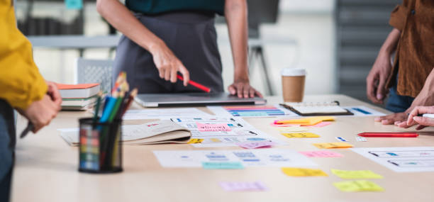 Close up ux developer and ui designer brainstorming about mobile app interface wireframe design on table with customer brief and color code at modern office.Creative digital development agency.panning stock photo