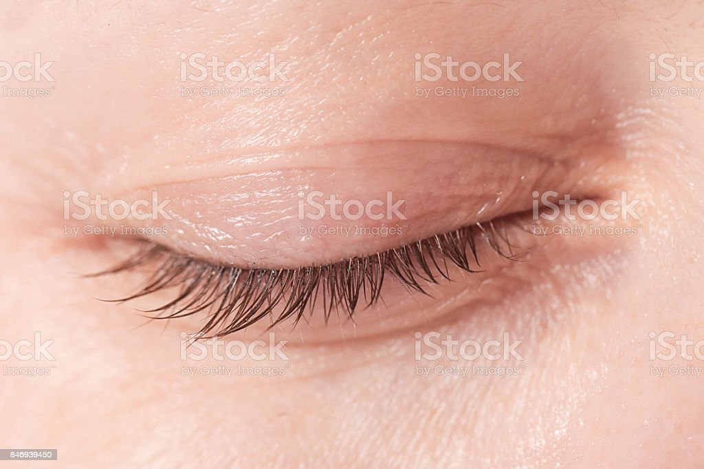 Close up view of a closed woman eye - no make up stock photo