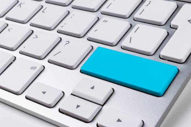 Close-up vista de um teclado de computador notebook com um botão azul na mesa do escritório branco, fundo de tecnologia, espaço vazio para texto - foto de acervo