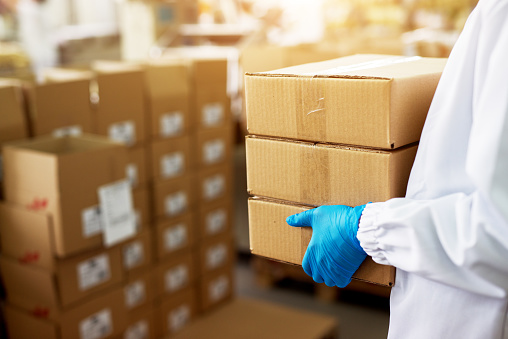 Close up view of a dedicated worker carrying a stack of duck taped brown boxes in factory storage room while wearing sterile cloths and rubber gloves.