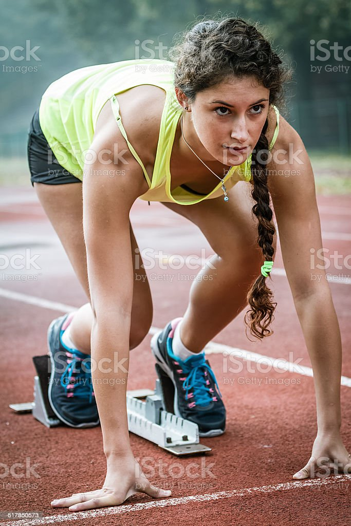 Close up view of a female sprinter ready to go stock photo
