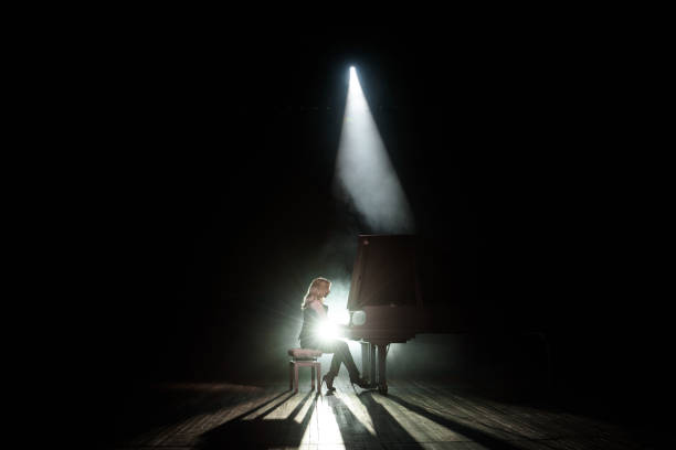 Close up view of a girl plays piano in the concert hall at scene Close up view of a girl plays piano in the concert hall at the scene pianist stock pictures, royalty-free photos & images