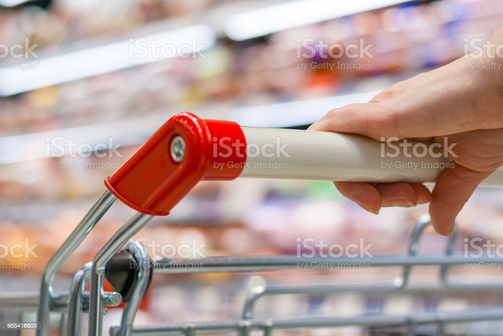 Close up view of a hand with pushcart in supermarket. The racks with the consumer goods in blur - Zbiór zdjęć royalty-free (Bez ludzi)