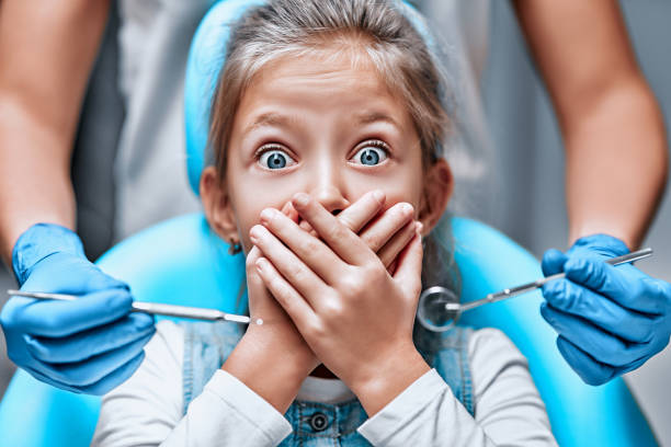 Close up view of a little girl looking scared and terrified screaming covering her mouth from the dentists with medical tools stock photo