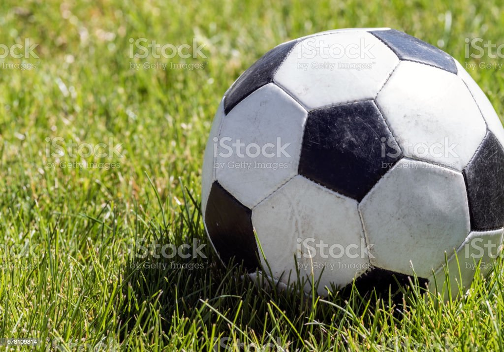 Close up view of a soccer ball or football on a green grassy field. stock photo