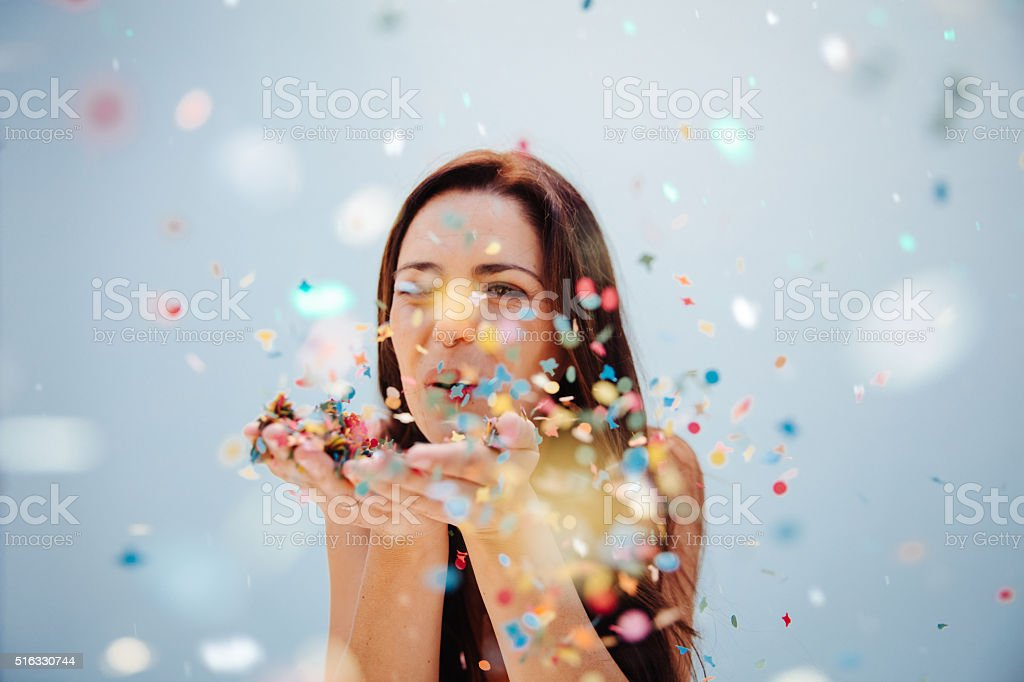 Close up view of a woman blowing confetti stock photo