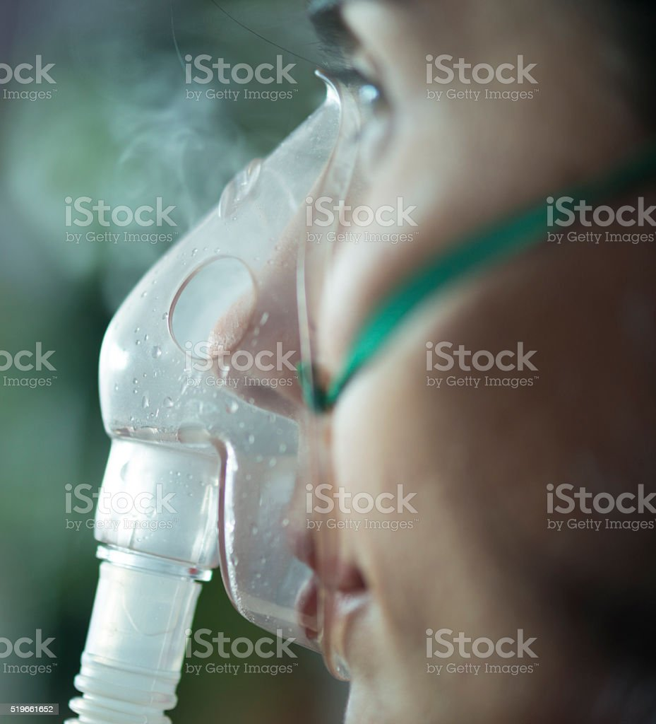 close up view of a woman  using nebuliser mask stock photo