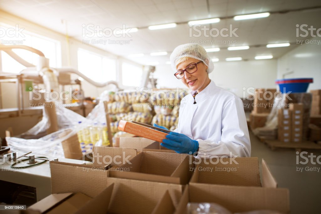 Close up view of a young female pleased worker in sterile cloths packing finished food products in a boxes in food factory storage. stock photo
