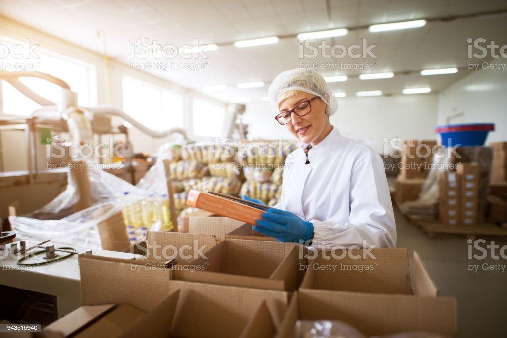 Gros plan de vue d'une jeune travailleuse heureuse en chiffons stériles d'emballage fini des produits alimentaires dans des boîtes un stockage usine alimentaire. - Photo