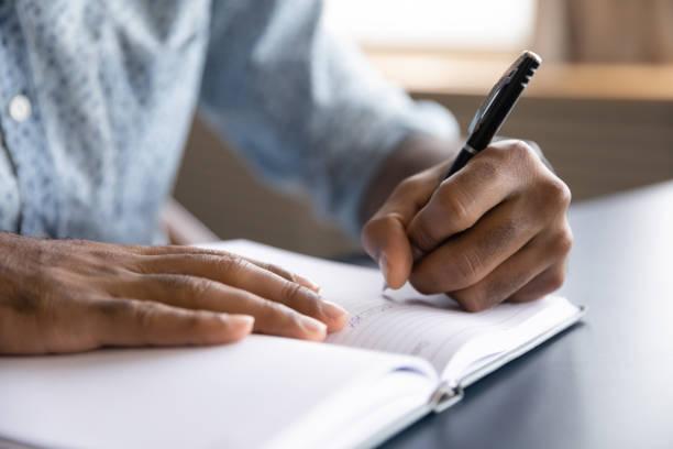 nahaufnahme des afrikanischen linkshänders, der in snotebook schreibt - handschrift stock-fotos und bilder
