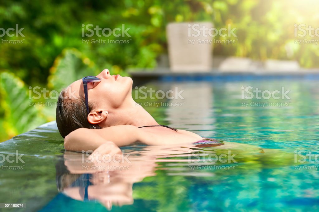 Close up view of an attractive young woman relaxing on a spa's swimming pool. stock photo