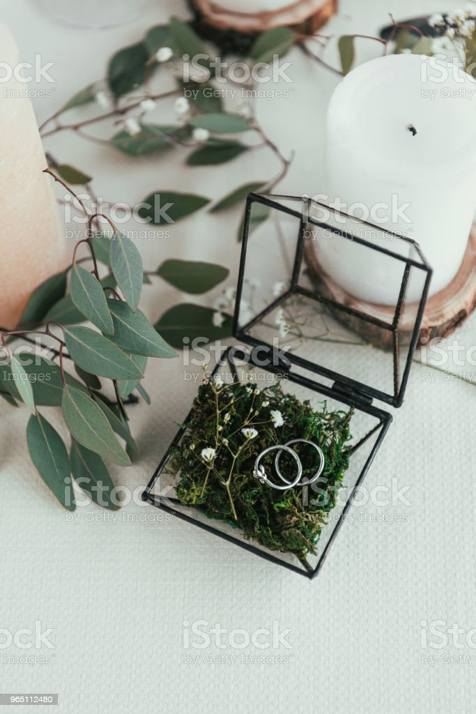 close up view of arranged candles, wedding rings in rustic box with plants inside zbiór zdjęć royalty-free