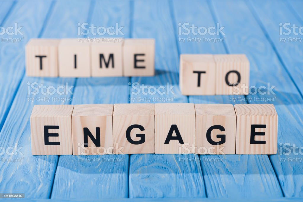 close up view of arranged wooden blocks into time to engage phrase on blue wooden surface stock photo