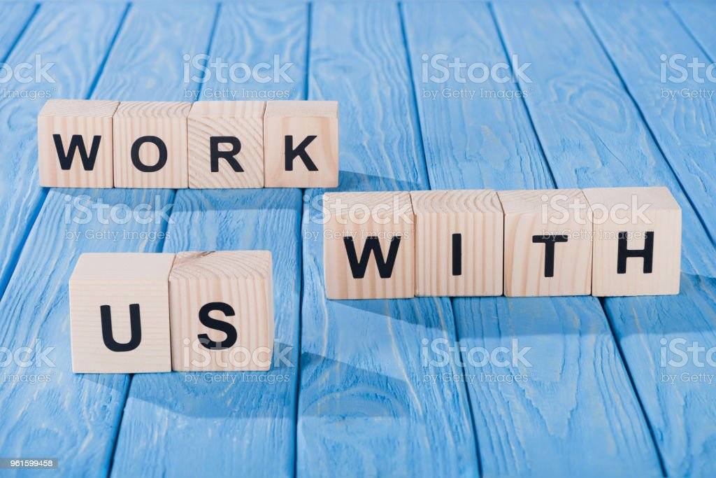 close up view of arranged wooden blocks into work with us phrase on blue wooden surface stock photo