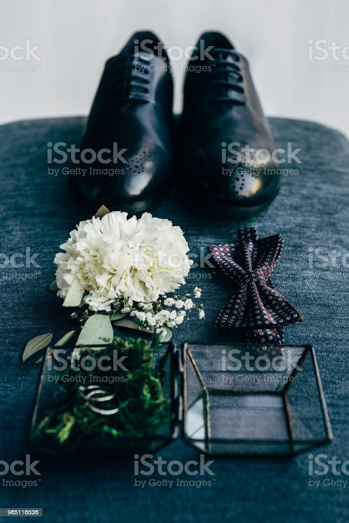 close up view of arrangement of grooms shoes, bow tie, corsage and wedding rings for rustic wedding on blue background royalty-free stock photo