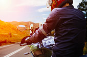 Close Up view of back of unrecognizable motor biker in helmet on motorcycle standing on edge of highway and looking on horizon with autumn  mountains at sunset.