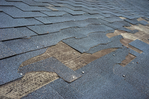 istock Close up view of bitumen shingles roof damage that needs repair. 1166557175