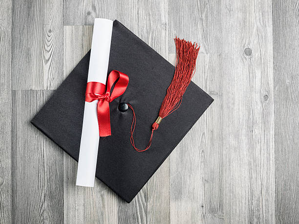 close up view of black graduation cap on wooden background - diploma stock photos and pictures