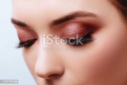istock Close up view of blue woman eye with beautiful golden shades and black eyeliner makeup. 1157731349
