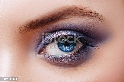 istock Close up view of blue woman eye with beautiful shades and black eyeliner makeup. 1157731378