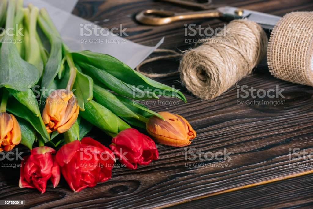 close up view of bouquet of tulips, ribbon, scissors and rope on wooden tabletop - Royalty-free Arrangement Stock Photo