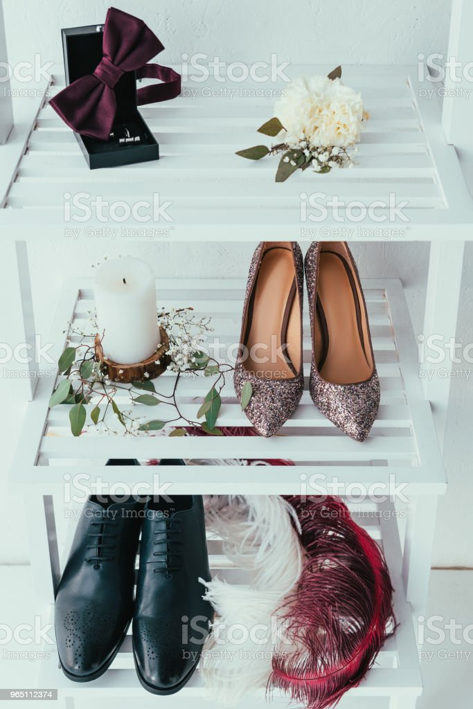 close up view of bridal and grooms shoes, candle and decorative feathers on grey backdrop royalty-free stock photo