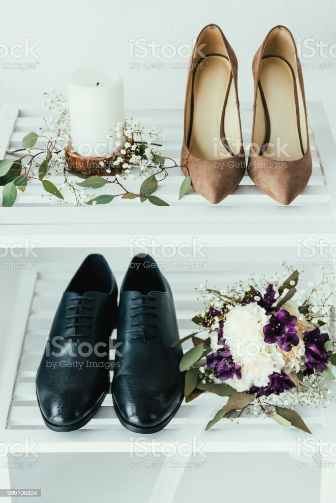 close up view of bridal and grooms shoes, candle and wedding bouquet on grey backdrop royalty-free stock photo