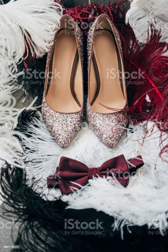 close up view of bridal shoes, grooms bow tie and feathers for rustic wedding royalty-free stock photo
