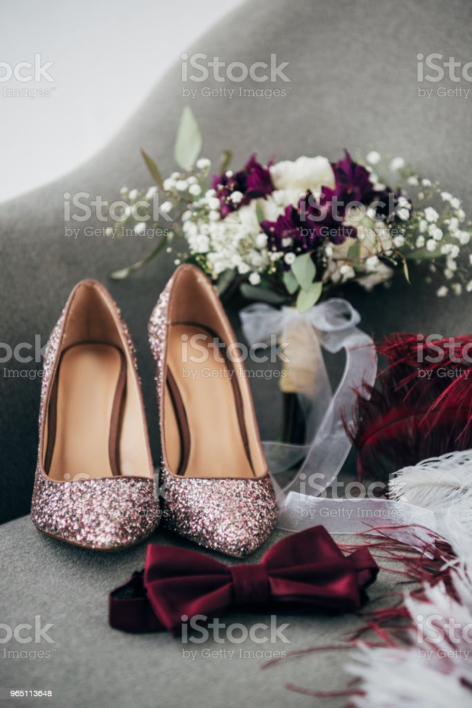 close up view of bridal shoes, grooms bow tie, wedding bouquet and feathers for rustic wedding on armchair zbiór zdjęć royalty-free