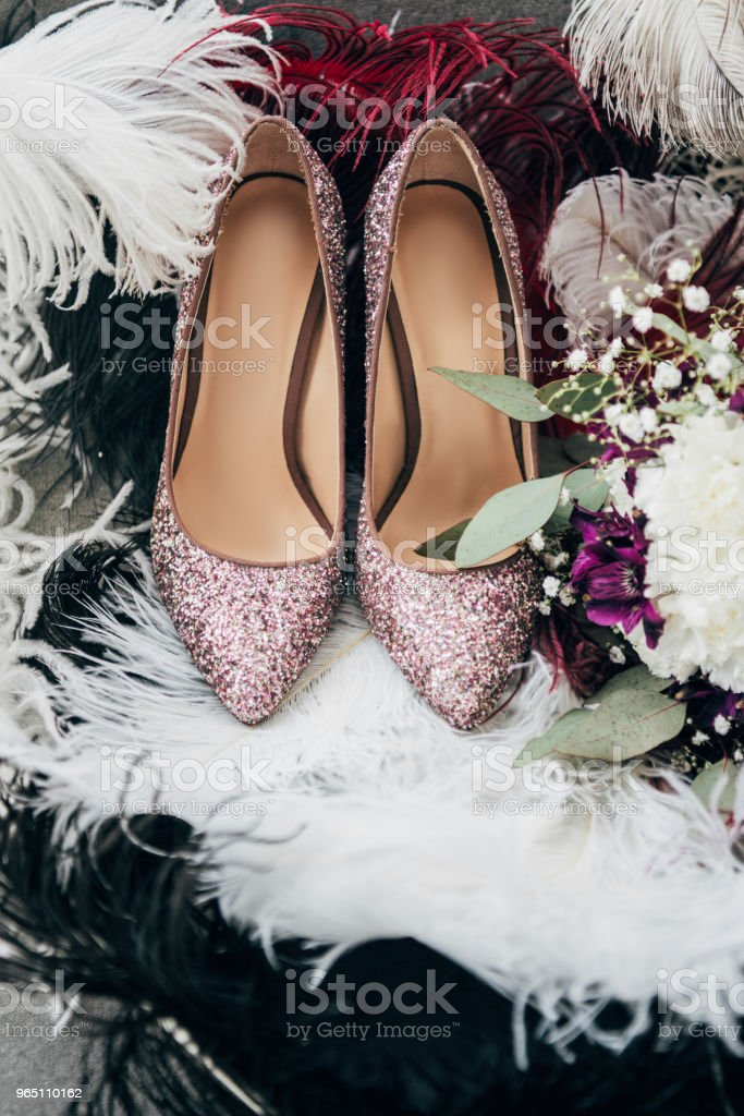 close up view of bridal shoes, wedding bouquet and feathers for rustic wedding royalty-free stock photo