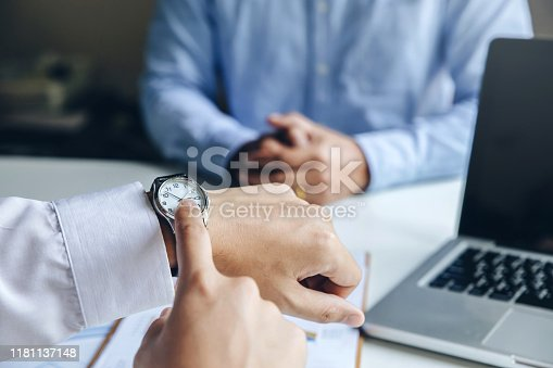 Close up view of businessman pointing on hand wristwatch