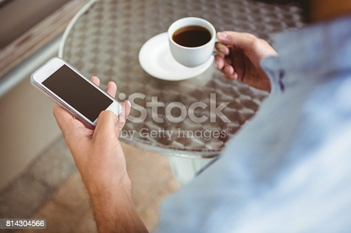 Close up view of businessman texting while holding cup of coffee