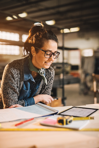 istock Close up view of charming smiling motivated middle aged industrial female engineer with eyeglasses working with blueprints and tablet in the workshop. 942008404