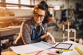 Close up view of charming smiling motivated middle aged industrial female engineer with eyeglasses working with blueprints and tablet in the workshop.