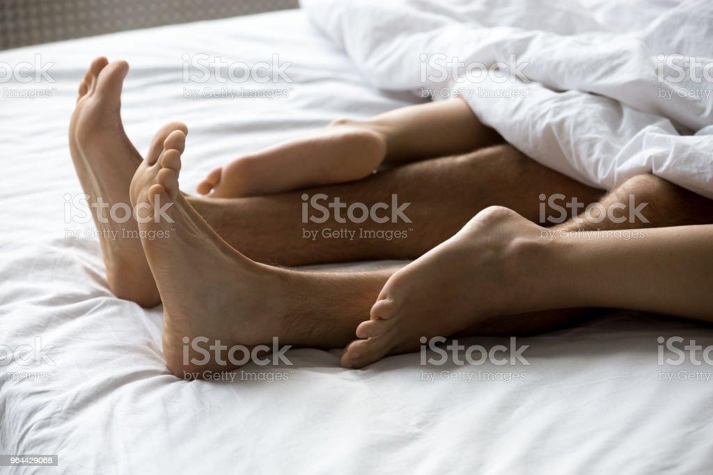 Close-up vista de pés casal fazendo amor na cama - Foto de stock de Aconchegante royalty-free