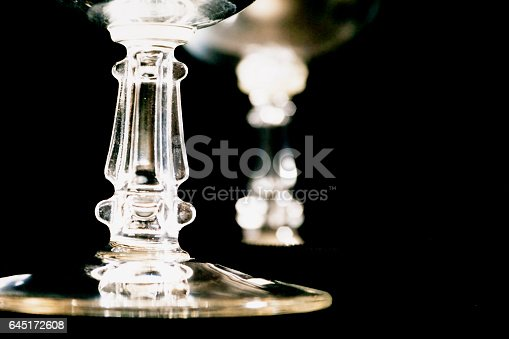 Close up view of crystal stemware glasses on black background.
