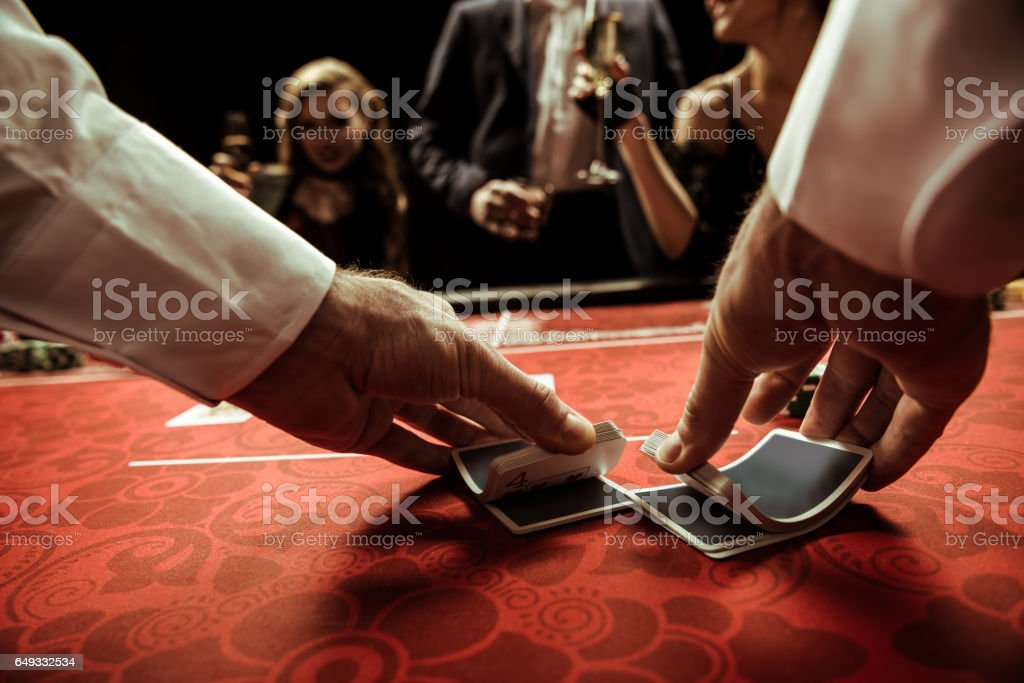 close up view of dealer shuffling cards in hands stock photo