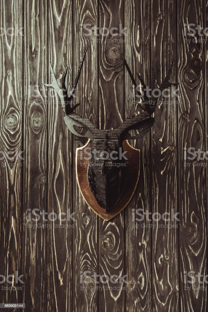 close up view of decorative wooden deer head on dark wooden surface - Royalty-free Backgrounds Stock Photo